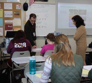 Ankeny High School teacher Joe Carey works with students after giving them an assignment based on his work last summer with InTrans' Basak Aldemir Bektas