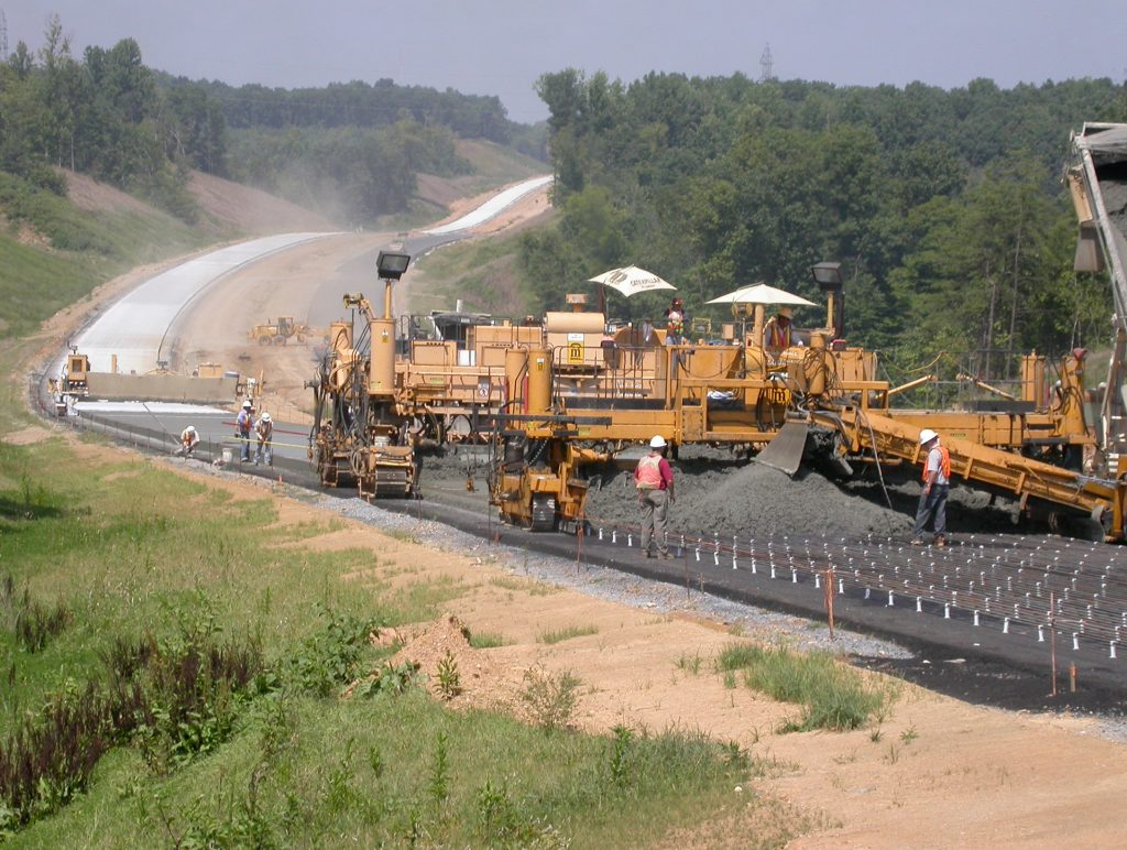 Image: Photograph shows a construction crew working on US 29 near Lynchburg, Virginia in 2004. The image shows workers and equipment laying and smoothing the base in the foreground; the new concrete roadway of the bypass is shown in the background on hilly terrain with trees on either side of the roadway.