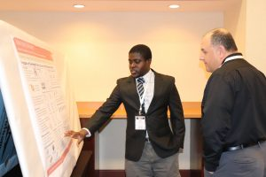 ISU PhD student Kofi Oppong discusses research into over-height truck collisions to bridge girders during the poster presentation session.