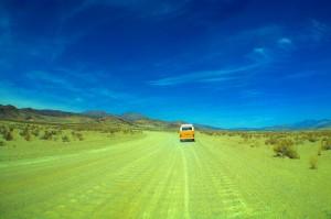 Yellow bus driving through desert.