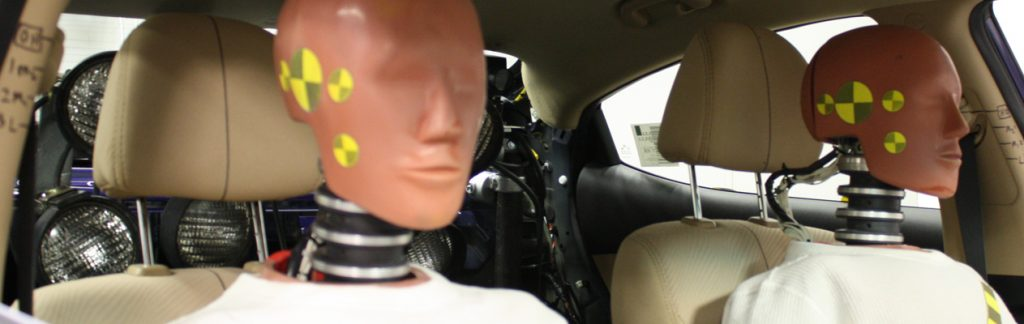 Driving dummies in the front and passenger seats of a car.