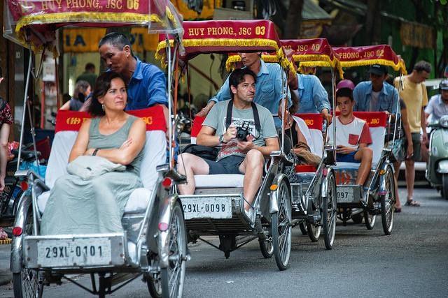 Tourists on cyclo in Hanoi, Vietnam.