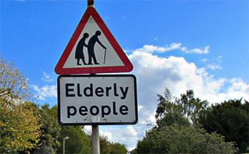 Road sign of elderly people crossing.