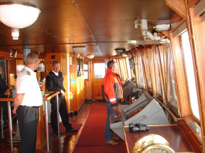 A master, seaman, and harbor pilot in a ship's wheelhouse