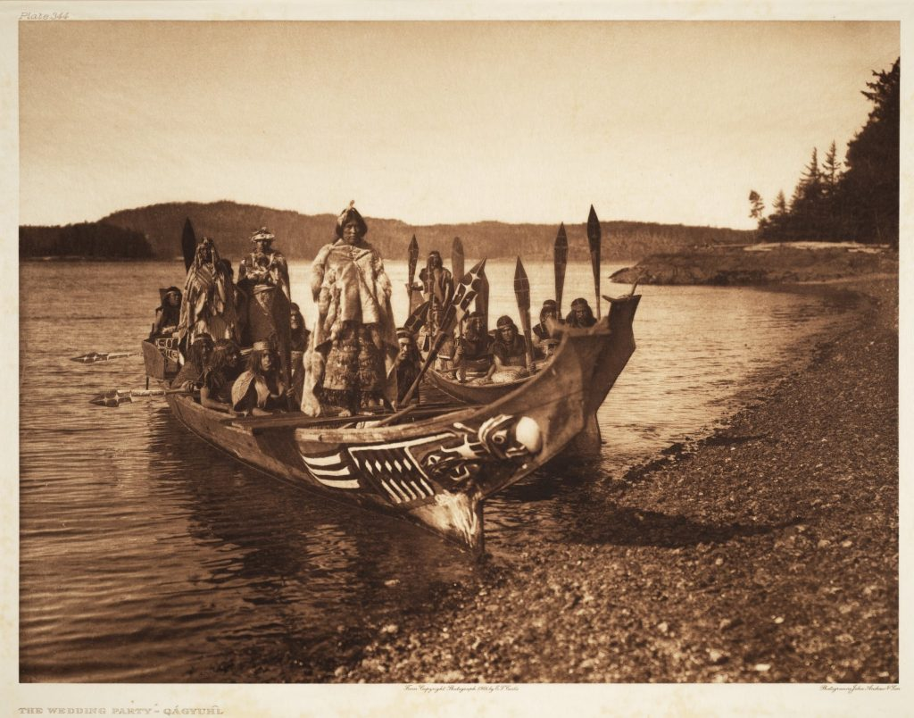 Northwest Coast Qagyuhl people aboard canoe for wedding party.