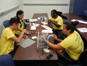 High school students at FIU's transportation camp design and build a balsa-wood bridge