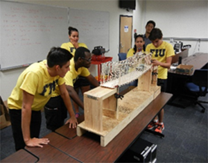 Using remote control toy cars, students at FIU's transportation camp test their balsa-wood bridge