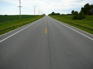 Two-lane rural Iowa highway with partially paved shoulders